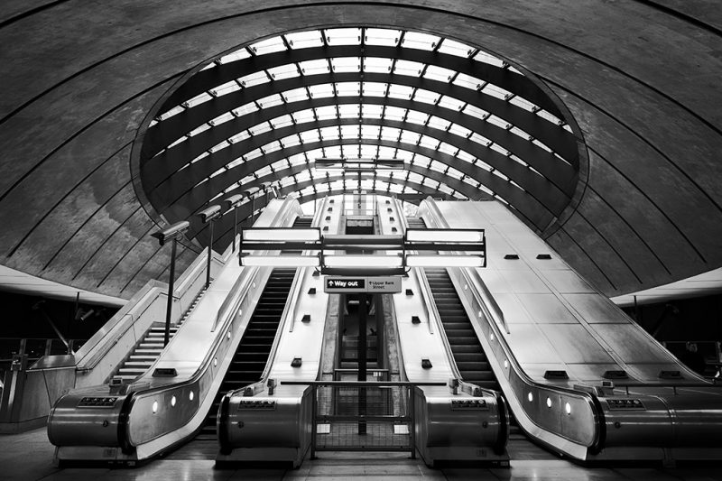 Black and white photograph of escalators at Canary Wharf Underground Station, London