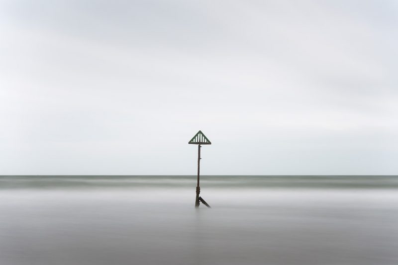 Black and white long exposure photograph of a marker post off West Wittering beach